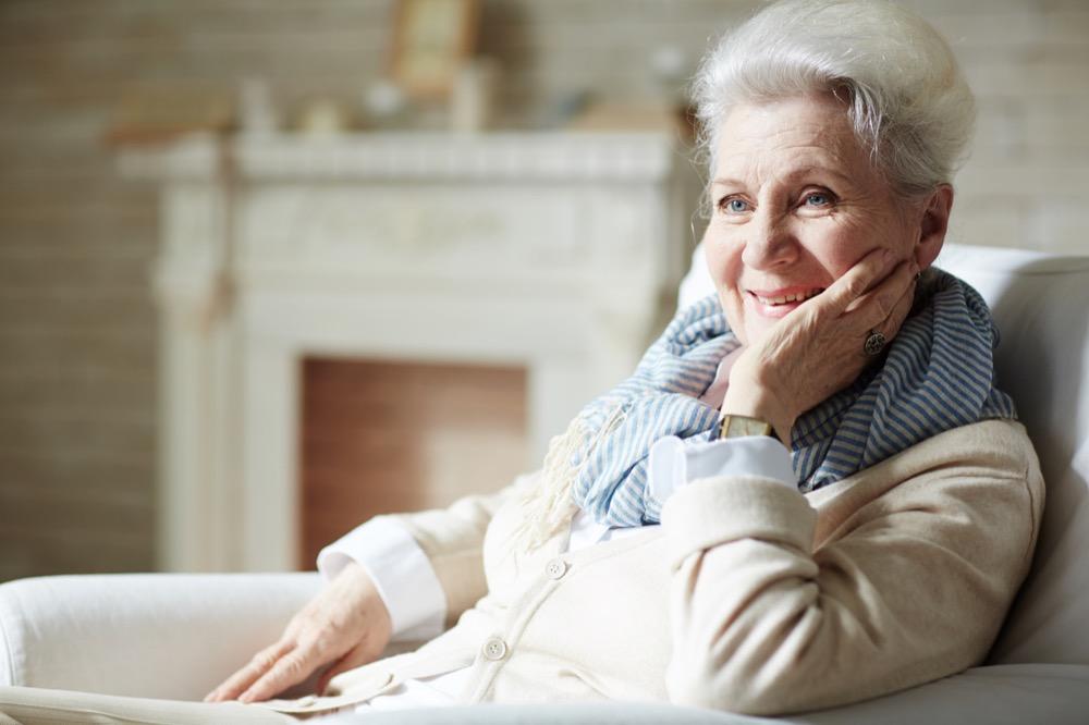 Illustration de l'autonomie des personnes âgées avec une femme de 70 ans souriante et confortable chez elle